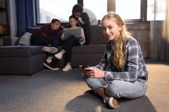 Adolescente que se sienta en piso y que usa smartphone con los amigos que usan el ordenador portátil detrás Fotografía de archivo libre de regalías