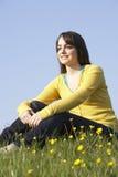 Adolescente que se sienta en prado del verano Fotos de archivo libres de regalías