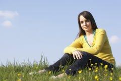 Adolescente que se sienta en prado del verano Imagen de archivo