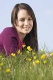 Adolescente que se sienta en prado del verano Foto de archivo libre de regalías