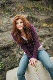 Adolescente que se sienta en roca Foto de archivo libre de regalías