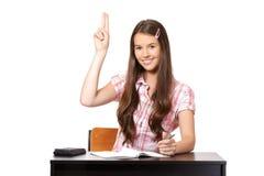Adolescente que se sienta en sala de clase con el raisedhand Foto de archivo libre de regalías