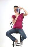 Adolescente que se sienta en silla con CD Fotos de archivo