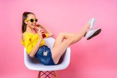 Adolescente que se sienta en silla y bebida de consumición Fotos de archivo libres de regalías