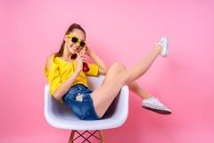 Adolescente que se sienta en silla y bebida de consumición Foto de archivo