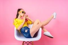 Adolescente que se sienta en silla y bebida de consumición Imagenes de archivo