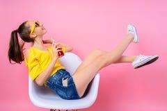 Adolescente que se sienta en silla y bebida de consumición Imagen de archivo libre de regalías