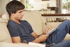 Adolescente que se sienta en Sofa At Home Doing Homework Imagen de archivo
