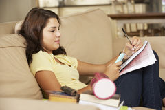 Adolescente que se sienta en Sofa At Home Doing Homework Imagenes de archivo