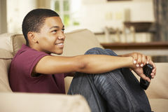 Adolescente que se sienta en Sofa At Home Watching Television Imagenes de archivo