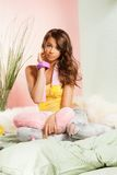Adolescente que se sienta en su cama Foto de archivo libre de regalías