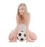 Adolescente que se sienta en suelo con el balón de fútbol Imagenes de archivo