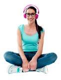 Adolescente que se sienta en suelo y música que escucha Foto de archivo libre de regalías