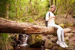 Adolescente que se sienta en un árbol en un bosque usando smartphone Imágenes de archivo libres de regalías