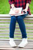 Adolescente que se sienta en un banco Imagenes de archivo