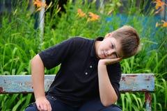 Adolescente que se sienta en un banco Imagen de archivo