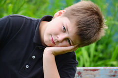 Adolescente que se sienta en un banco Fotos de archivo
