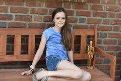 Adolescente que se sienta en un banco Fotos de archivo libres de regalías