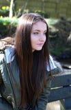 Adolescente que se sienta en un banco de parque en un día frío Imágenes de archivo libres de regalías