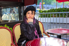 Adolescente que se sienta en un café de la tabla en el Champs-Elysees, París, F Imagen de archivo libre de regalías