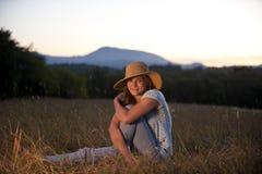 Adolescente que se sienta en un campo Imagen de archivo libre de regalías