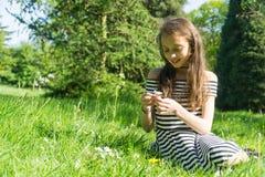 Adolescente que se sienta en un campo de la margarita Fotos de archivo libres de regalías