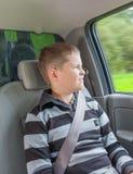 Adolescente que se sienta en un coche en silla de la seguridad Fotografía de archivo