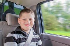 Adolescente que se sienta en un coche en silla de la seguridad Imagen de archivo