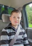 Adolescente que se sienta en un coche en silla de la seguridad Imagen de archivo libre de regalías