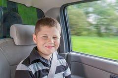 Adolescente que se sienta en un coche en silla de la seguridad Foto de archivo