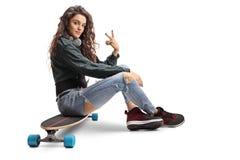 Adolescente que se sienta en un longboard y que hace un gesto de la paz Fotografía de archivo libre de regalías