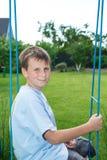 Adolescente que se sienta en un oscilación Fotografía de archivo