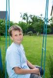 Adolescente que se sienta en un oscilación Fotos de archivo libres de regalías
