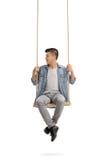 Adolescente que se sienta en un oscilación y que mira a la izquierda Fotografía de archivo libre de regalías