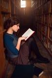 Adolescente que se sienta en un piso de la biblioteca y leído Imagen de archivo libre de regalías