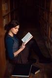 Adolescente que se sienta en un piso de la biblioteca y leído Fotos de archivo libres de regalías
