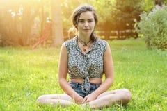 Adolescente que se sienta en un prado Imagen de archivo