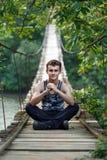 Adolescente que se sienta en un puente Fotografía de archivo libre de regalías