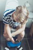 Adolescente que se sienta en un retrete con su móvil Fotografía de archivo libre de regalías