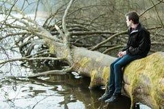 Adolescente que se sienta en un tronco de árbol caido Fotos de archivo