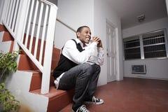 Adolescente que se sienta en una escalera Imagenes de archivo