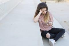 Adolescente que se sienta en una escalera con su mirada móvil Imagenes de archivo