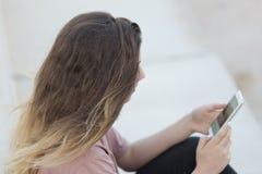 Adolescente que se sienta en una escalera con su mirada móvil Imágenes de archivo libres de regalías