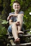 Adolescente que se sienta en una escalera de madera, sonriendo Imagen de archivo libre de regalías