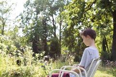 Adolescente que se sienta en una silla Imagenes de archivo