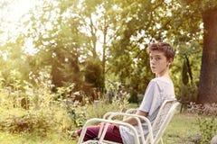 Adolescente que se sienta en una silla Imagen de archivo libre de regalías