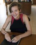 Adolescente que se sienta en una tabla con el teléfono celular y el cuaderno Fotografía de archivo libre de regalías
