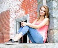Adolescente que se sienta en ventana Fotos de archivo libres de regalías