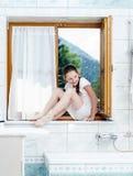 Adolescente que se sienta en ventana del cuarto de baño Foto de archivo