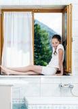 Adolescente que se sienta en ventana del cuarto de baño Imagen de archivo libre de regalías